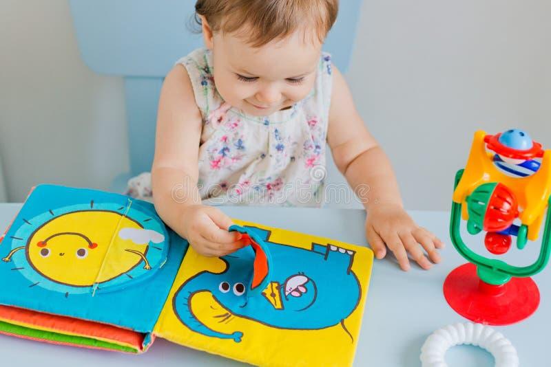 Kleines Kind, das mit weichem Buch spielt stockbild
