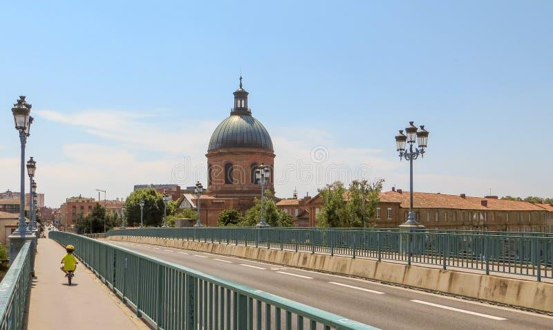 Kleines Kind, das sicher Fahrrad in Radweg auf eine szenische europäische Brücke fährt stockfotografie