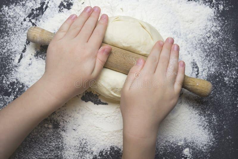 Kleines Kind, das Teig für das Zurückziehen zubereitet Scherzen Sie ` s Hände, etwas Mehl, Weizenteig und Nudelholz auf der schwa lizenzfreies stockbild