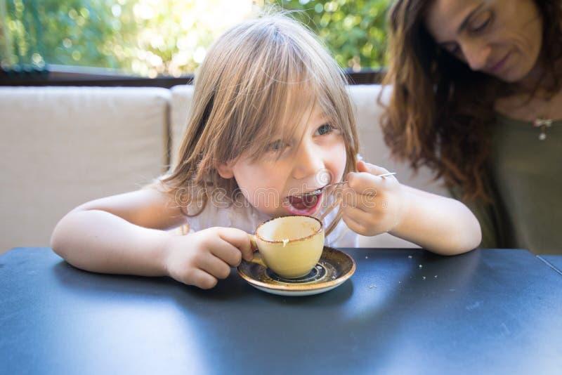 Kleines Kind, das Zucker mit Löffel von der Kaffeetasse isst stockbild