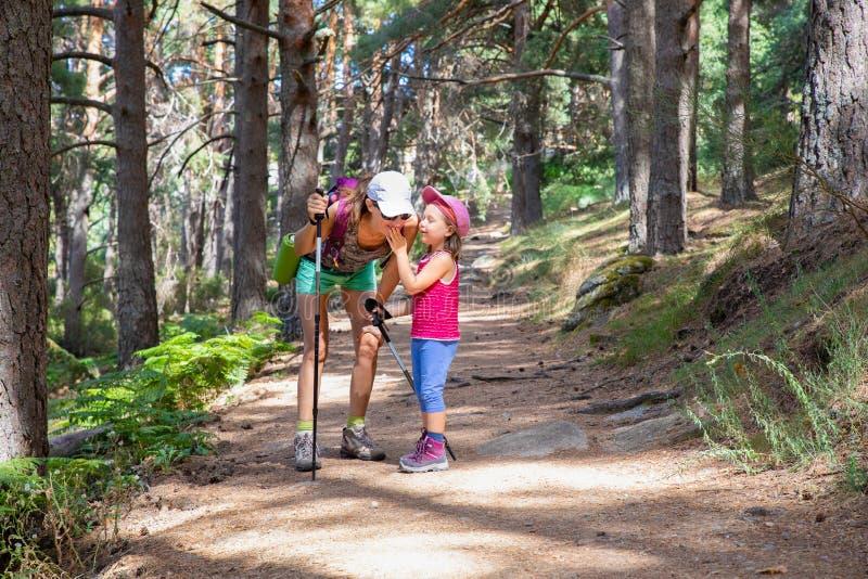 Kleines Kind des Bergsteigers, das mit Frau auf einem Fußweg im Wald lacht und spricht stockfotos