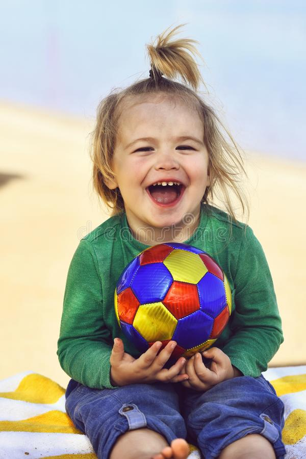 Kleines Kind des entzückenden Jungen mit dem glücklichen lächelnden Gesicht, das Ball hält stockbilder