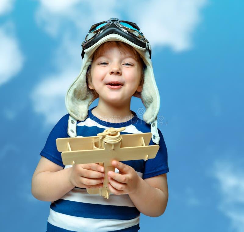 Kleines Kind des Porträts, das mit einem Flugzeug, abstraktes backgrou spielt lizenzfreie stockbilder