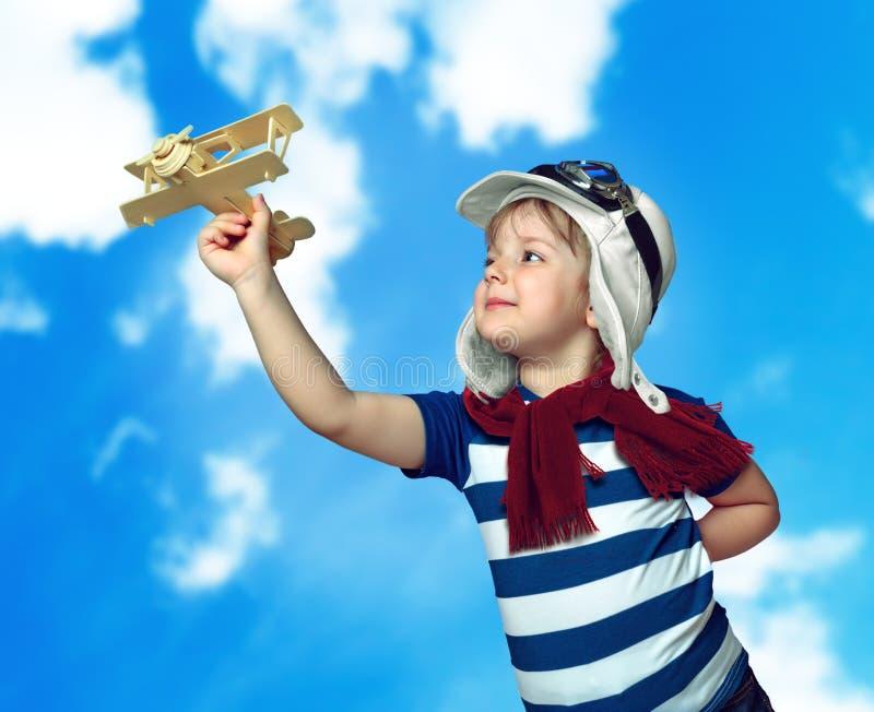 Kleines Kind des Porträts, das mit einem Flugzeug, abstraktes backgrou spielt lizenzfreie stockfotografie
