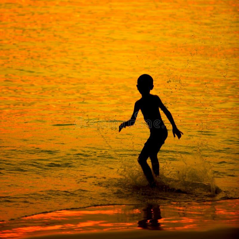 Kleines Kind des Schattenbildes auf einem Strand lizenzfreies stockfoto