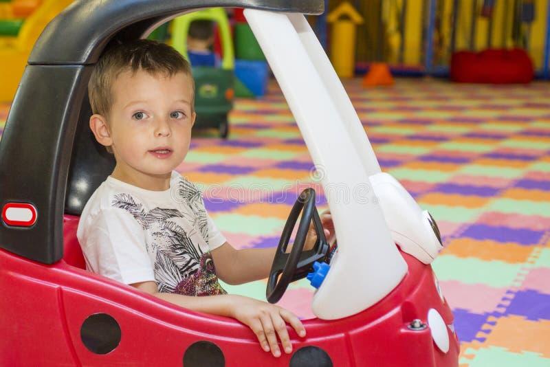 Kleines Kind in einem roten Spielzeugauto am Innenspielplatz Junge im Kind-` s Auto stockfoto