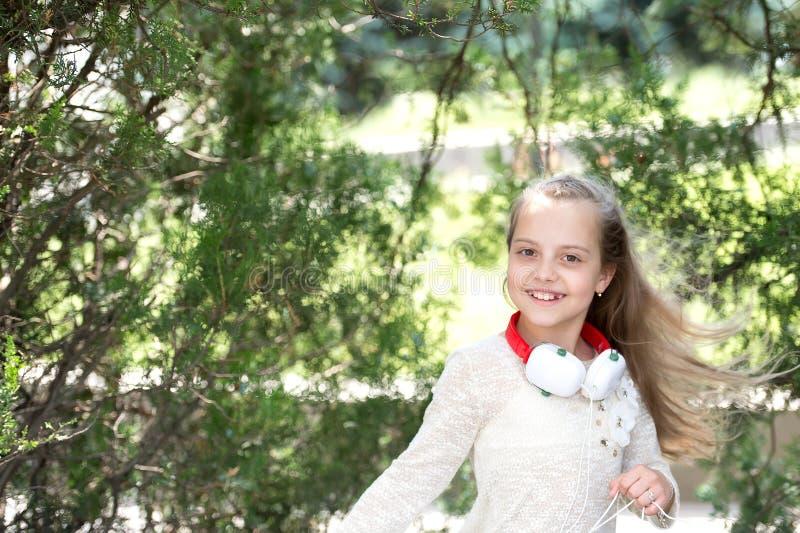 Kleines Kind genießen Musik Kopfhörern in den im Freien Glücklicher Mädchentanz zur Musik im Sommerpark Kindertänzerlächeln mit l stockfotos