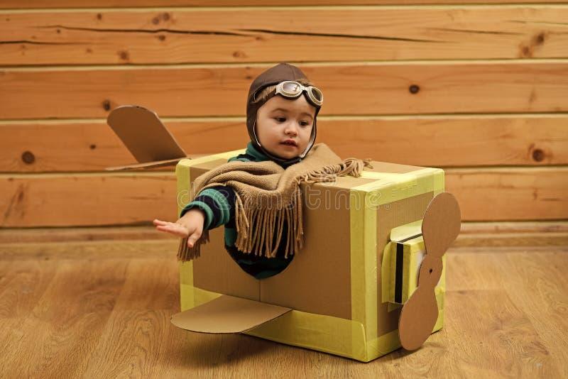 Kleines Kind im Piloten Costume Dreaming Of, welches das Flugzeug steuert stockfotografie