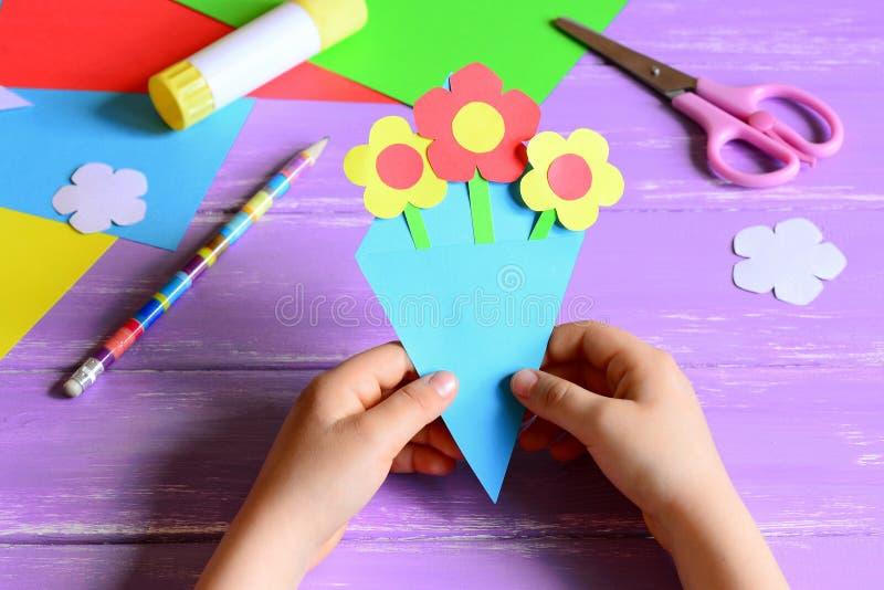 Kleines Kind machte Papierhandwerk für Mutter ` s Tag oder Geburtstag Kind hält einen Papierblumenstrauß in den Händen Einfaches  lizenzfreie stockfotos