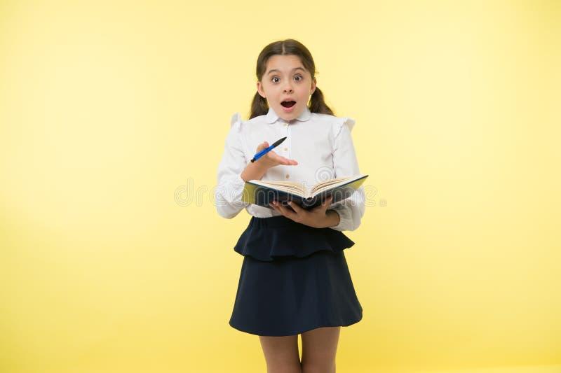 Kleines Kind mit überraschtem Blick Schulmädchen mit langem Haargriffbuch mit Stift Modegenie Zurück zu Schule Haus lizenzfreies stockfoto