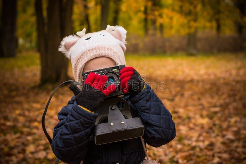 Kleines Kind mit der alten Retro- Kamera, die draußen Foto tut Porträt des Kindes des kleinen Mädchens mit Retro- Weinlesespiegel lizenzfreies stockfoto