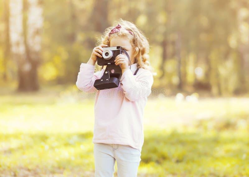 Kleines Kind mit der alten Retro- Kamera, die Foto tut lizenzfreie stockfotografie