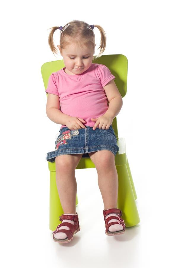 Kleines Kind sitzt auf einem Stuhl lizenzfreies stockfoto