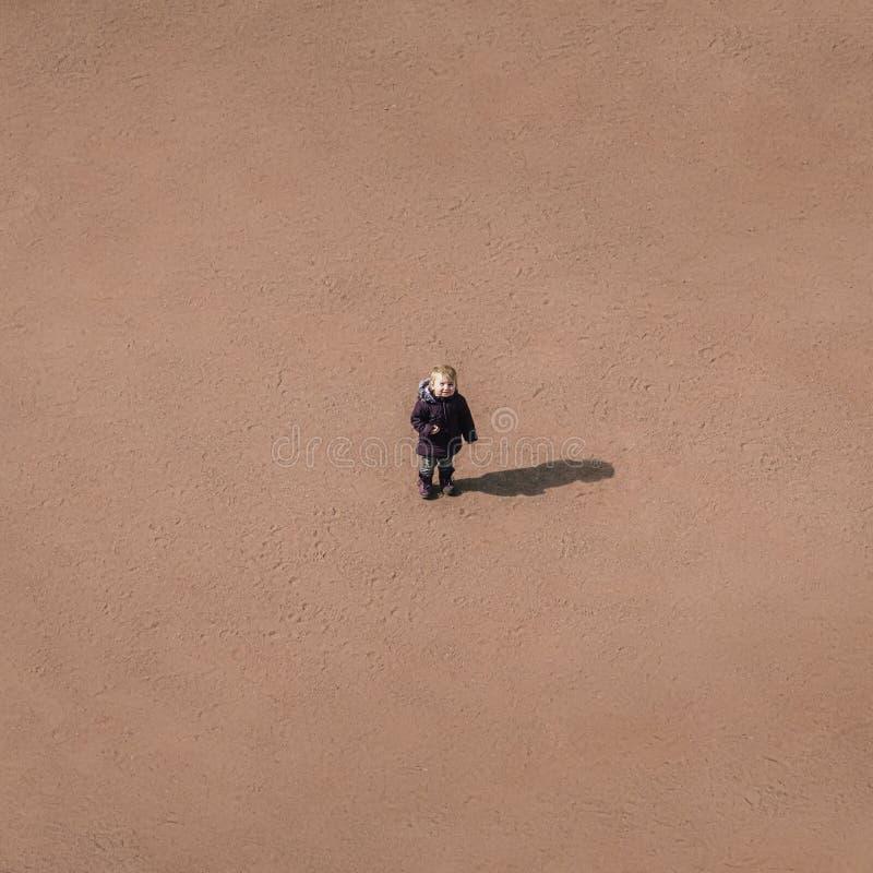 Kleines Kind steht mitten in einer Sandwüste, ein conce lizenzfreie stockbilder
