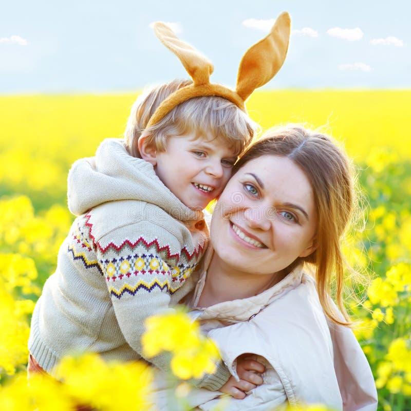 Kleines Kind und seine Mutter in den Osterhasenohren, die den Spaß, traditionellen Ostern-Feiertag feiernd haben Kinderkleinkindj lizenzfreies stockbild