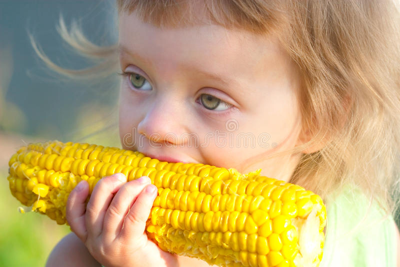 Kleines Kind, zum des gekochten Maiskolbens zu essen stockbilder