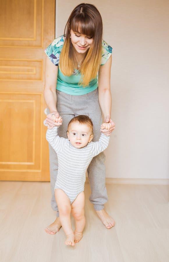 Kleines Kinderbaby, das erste Schritte machend lächelt stockfotos
