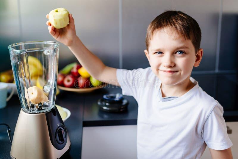 Kleines Kinderjunge, der Apfel zur Mischmaschine setzt lizenzfreies stockbild
