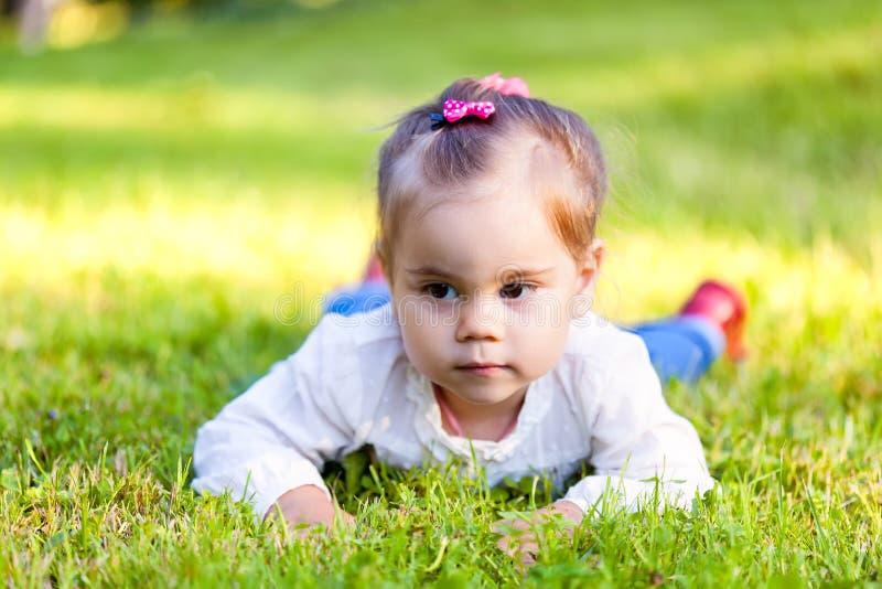 Kleines Kindermädchen, das auf Feld liegt lizenzfreies stockbild