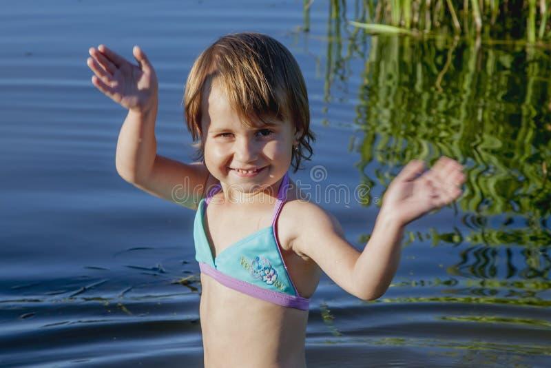 Kleines Kindermädchen steigen in das Wasser des Sees ein zu schwimmen holida stockfoto