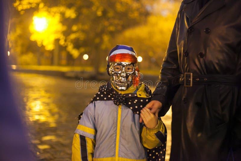Kleines Kindertragende Schädelmaske, begleitet von einem Erwachsenen stockbilder