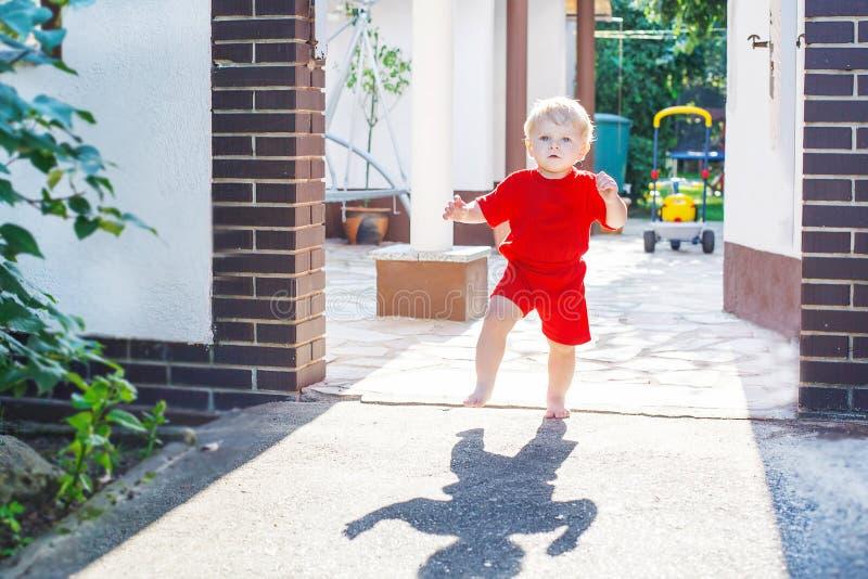 Kleines Kleinkindbaby, das draußen seine ersten Schritte macht stockfoto