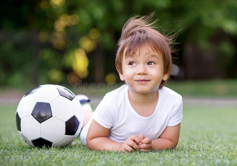 Kleines Kleinkindkind, das auf Bauch auf Fußballplatz nahe Fußball und dem Träumen legt Wind bewegt Haar des Kindes wellenartig Z lizenzfreie stockfotos