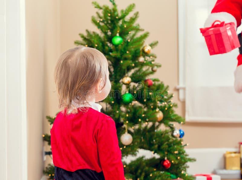 Kleines Kleinkindmädchen, das ein Geschenk von Santa Claus erhält stockbild