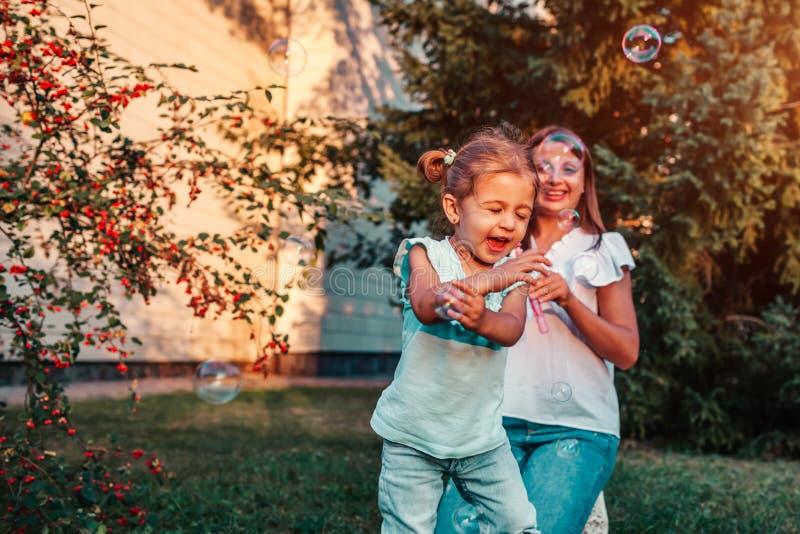 Kleines Kleinkindmädchen, das mit Seifenblasen spielt, die ihre Mutter im Sommerpark durchbrennt Glückliches Kind, das Spaß drauß stockbild