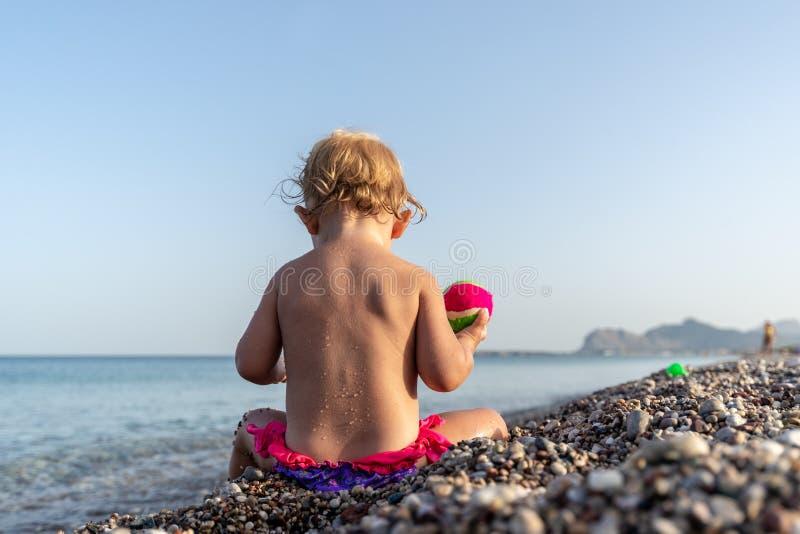Kleines Kleinkindmädchen im rosa Badeanzug, der auf schönem Pebble Beach sitzt stockfoto
