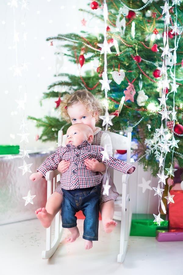 Kleines Kleinkindmädchen und ihr neugeborener Babybruder unter Weihnachtsbaum stockfoto