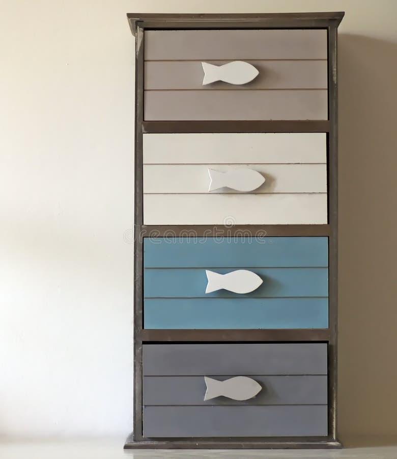 Kleines Kommode mit Fisch-förmigen Griffen und vier Fächern von verschiedenen und weichen Farben stockbilder