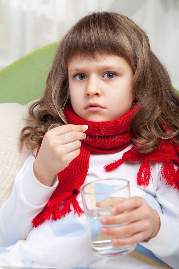 Kleines krankes Mädchen im Bett nimmt eine Pille lizenzfreie stockbilder