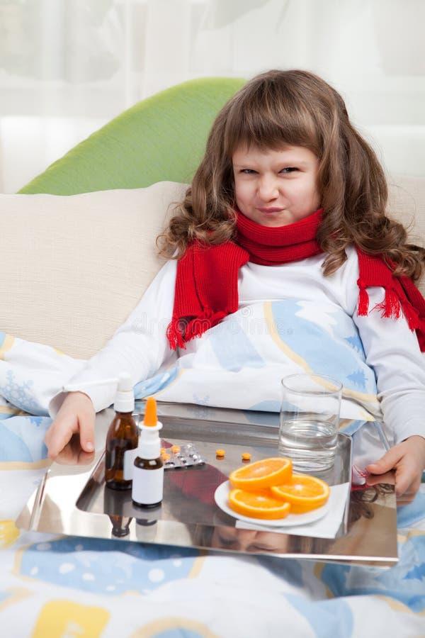 Kleines krankes Mädchen im Bett nimmt Medizin stockfotos