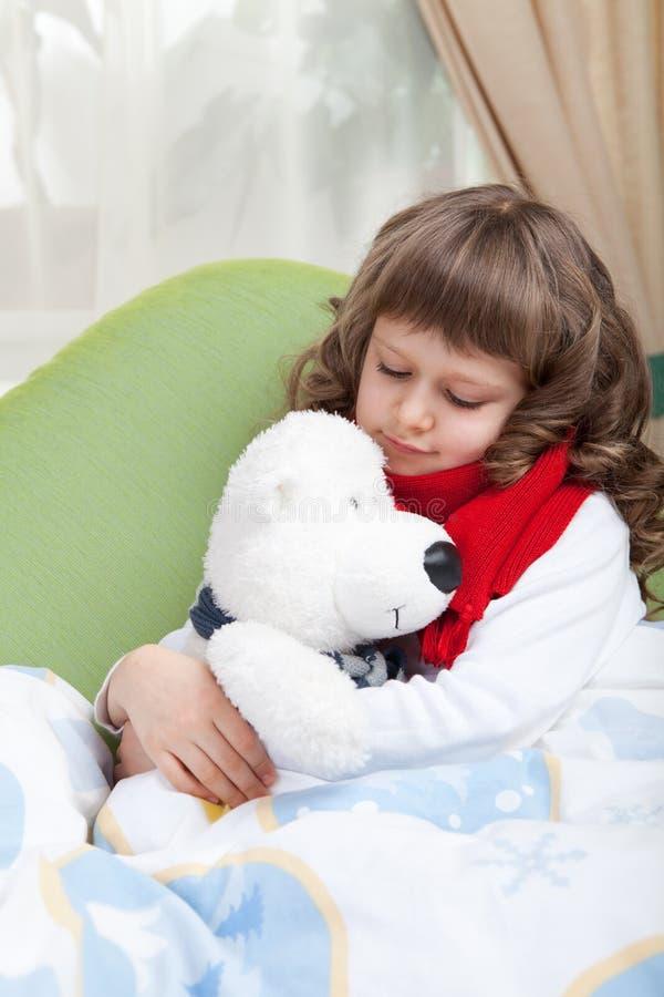 Kleines krankes Mädchen mit Schal umfaßt Spielzeugbären lizenzfreies stockbild