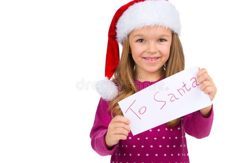 Kleines lächelndes Mädchen, das Buchstaben für Santa Claus hält. stockbilder