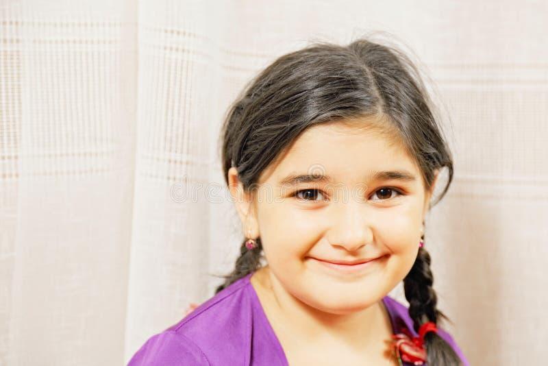 Kleines lächelndes Mädchen im purpurroten Kleid lizenzfreie stockfotografie