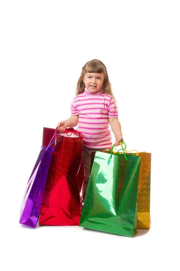 Kleines lächelndes Mädchen mit Beuteln lizenzfreies stockbild