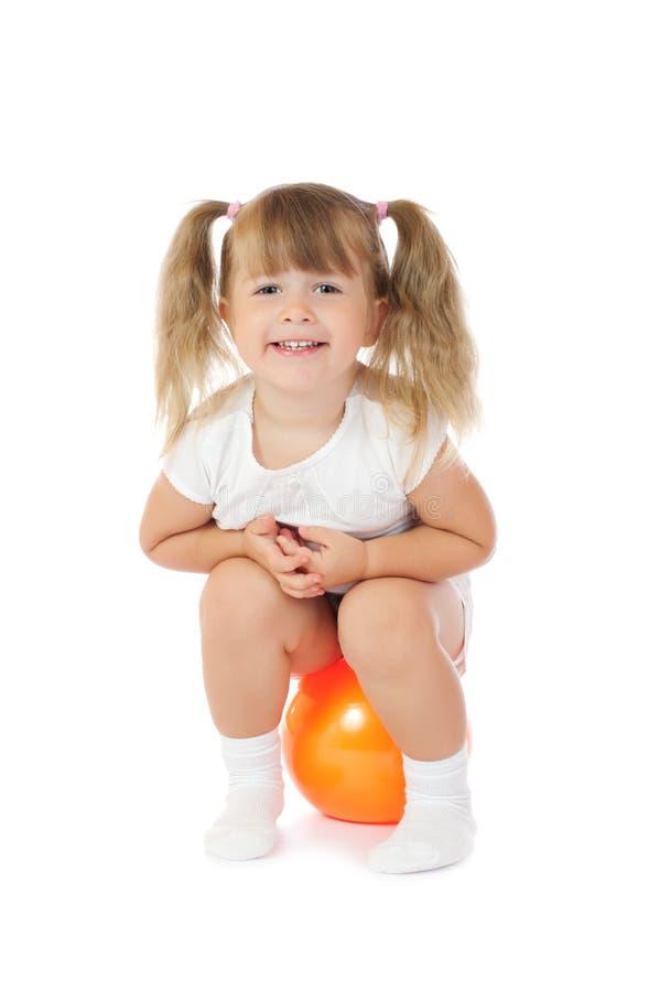 Kleines lächelndes Mädchen mit Kugel stockfotos