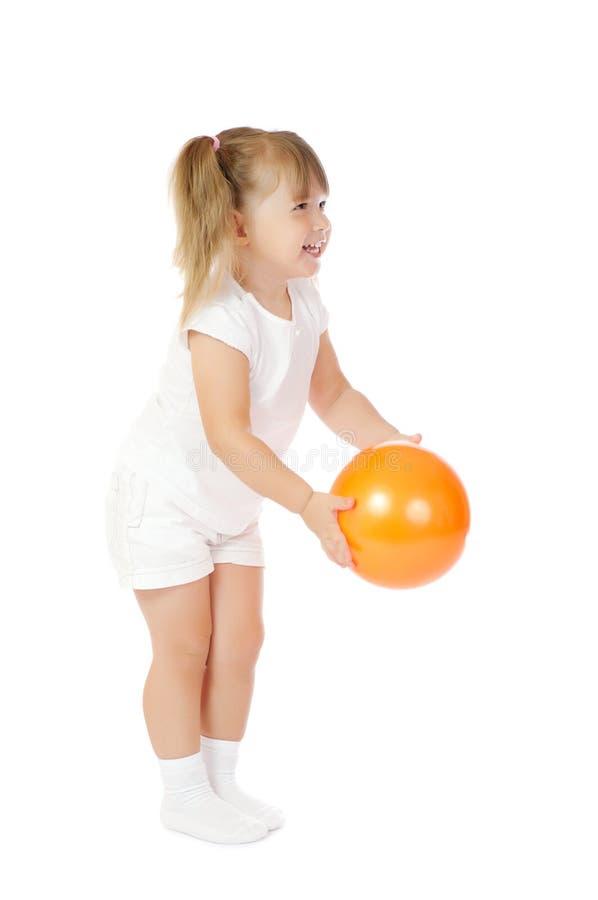 Kleines lächelndes Mädchen mit Kugel stockbilder