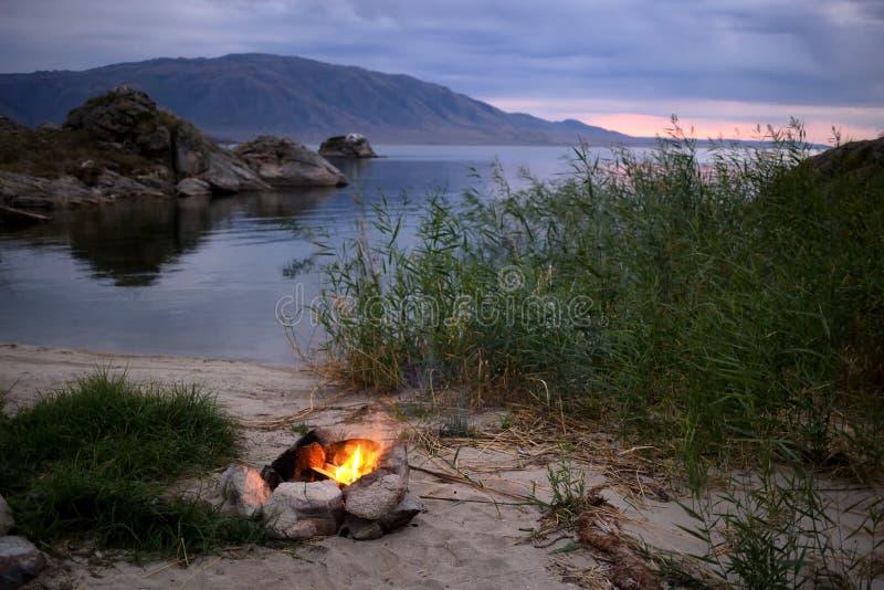 Kleines Lagerfeuer auf dem Ufer von See stockbilder