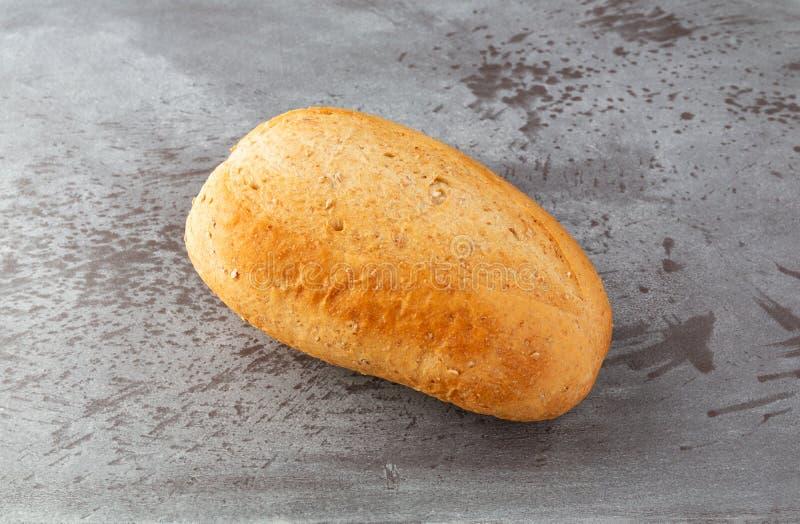 Kleines Laib des Weizenbrotes auf einem grauen gesprenkelten Hintergrund stockfoto