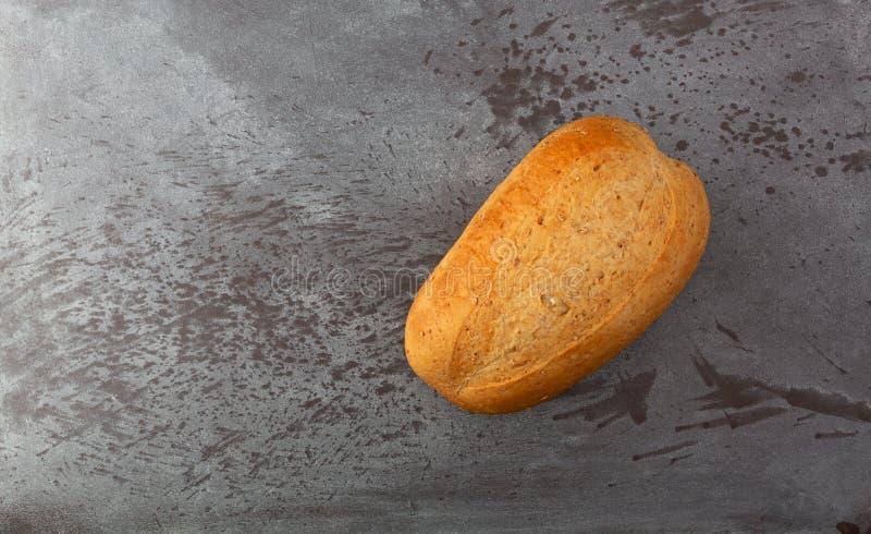 Kleines Laib des Weizenbrotes ausgeglichen auf einer grauen gesprenkelten Draufsicht des Hintergrundes lizenzfreies stockfoto