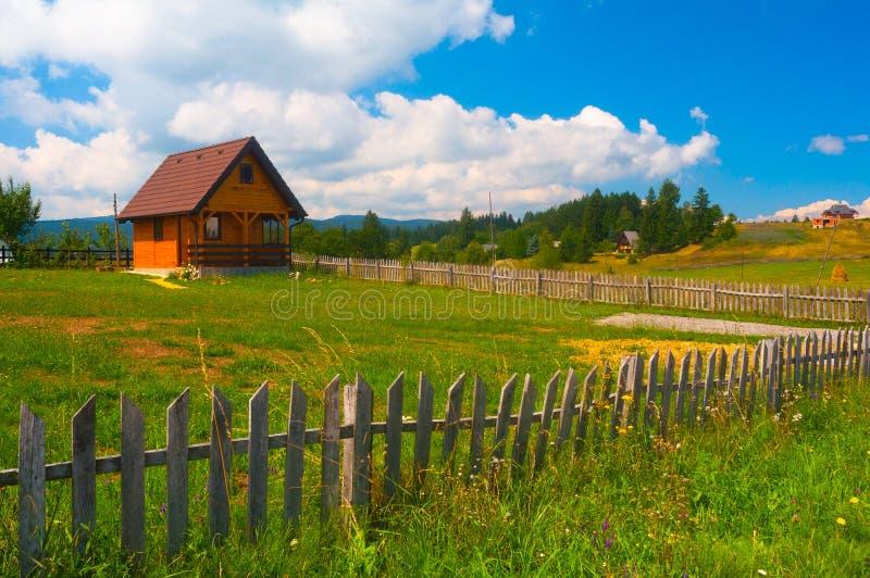 Kleines Landhaus, Wiese und hölzerner Zaun lizenzfreies stockfoto