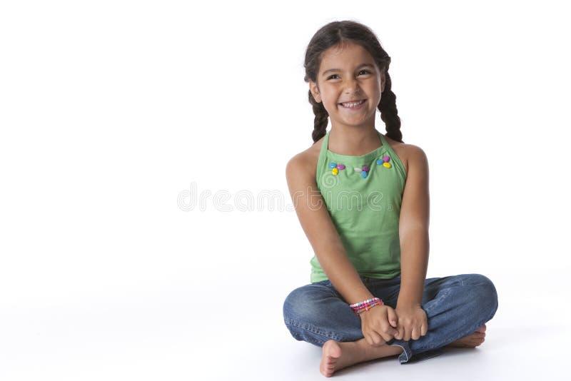 Kleines lustiges Mädchen, das auf dem Fußboden sitzt lizenzfreie stockbilder