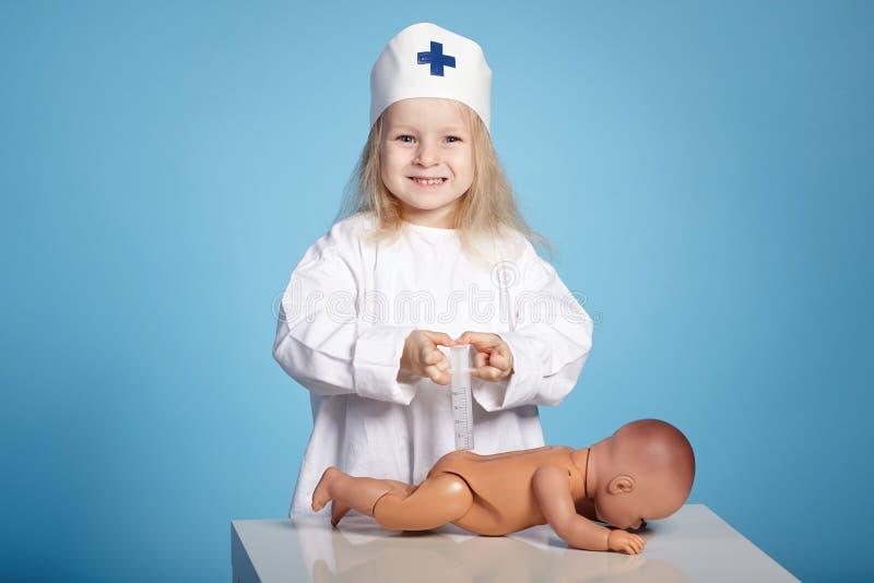 Kleines lustiges Mädchen, das Krankenschwester spielt stockfotografie