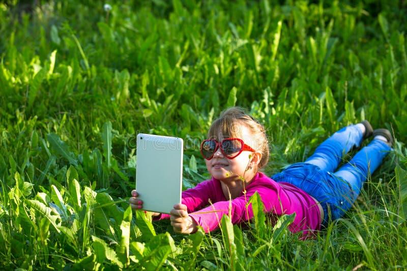 Kleines lustiges Mädchen mit einer Tablette macht ein Selbstporträt, das im grünen Gras liegt stockfotografie