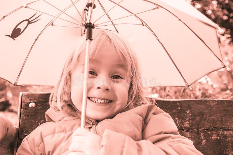 kleines lustiges Mädchen unter einem Regenschirm, Porträt lizenzfreie stockbilder