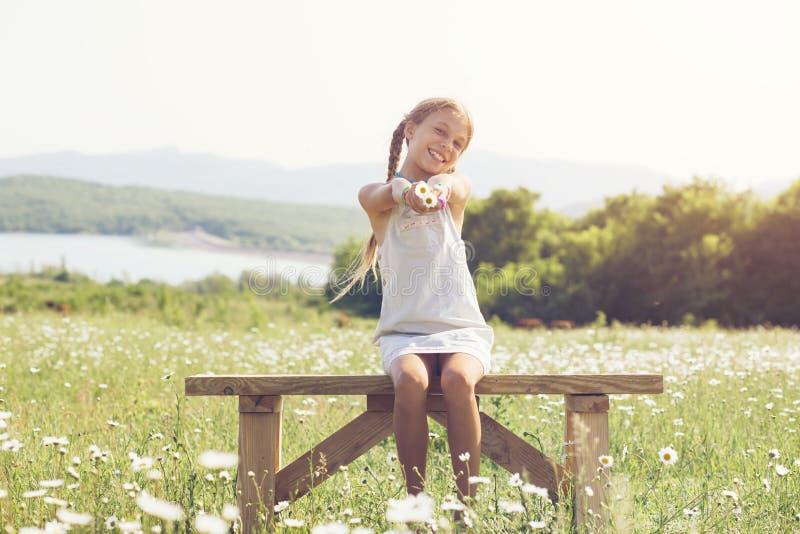 Kleines Mädchen auf dem Blumengebiet stockfoto