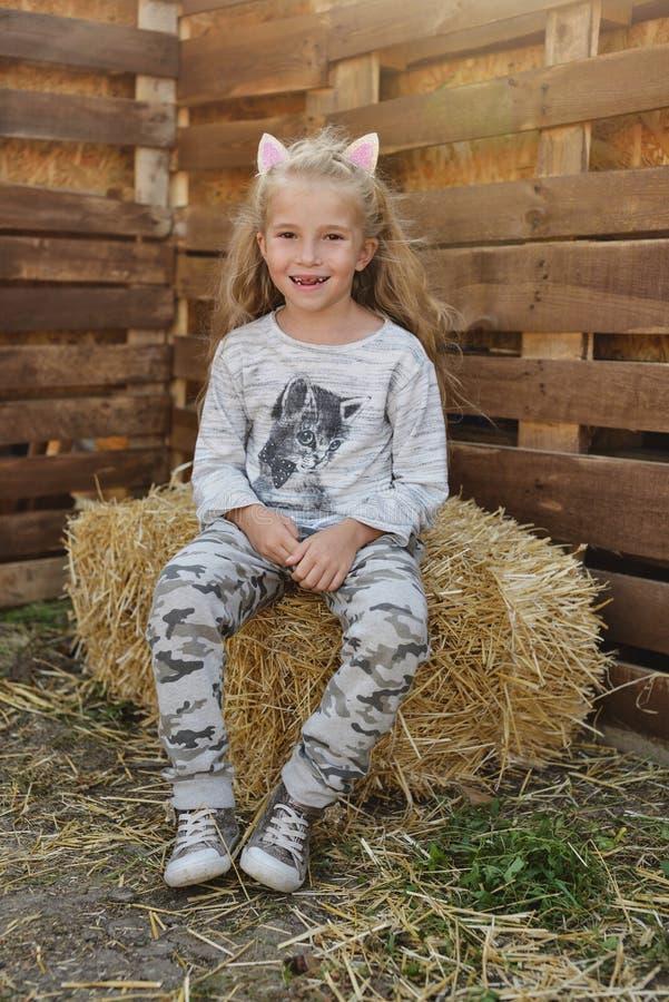 Kleines Mädchen auf dem Heu lizenzfreie stockfotos